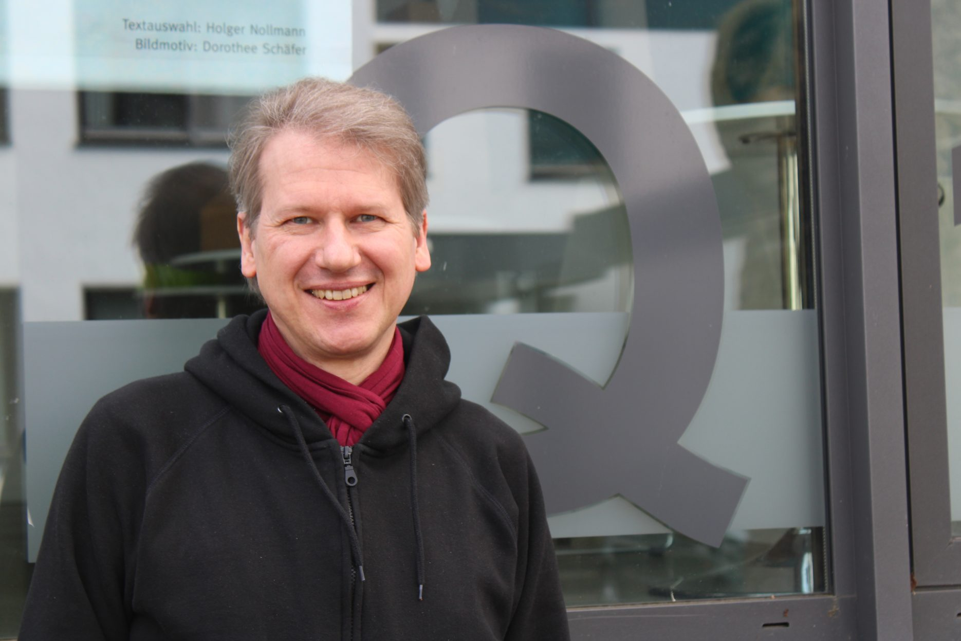Westend-Techniker Michael Kallweitt vor der Glasfassade des Q1